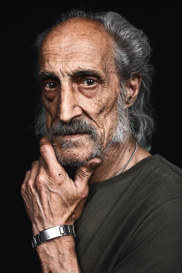 Maschio anziano barbuto serio in maglietta che pensa a Laon, soldi, immagini stock