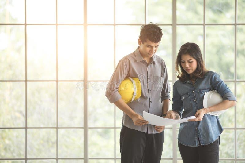 Maschio asiatico due ed ingegneri femminili che tengono il casco di sicurezza bianco e giallo che sta insieme e che parla immagine stock