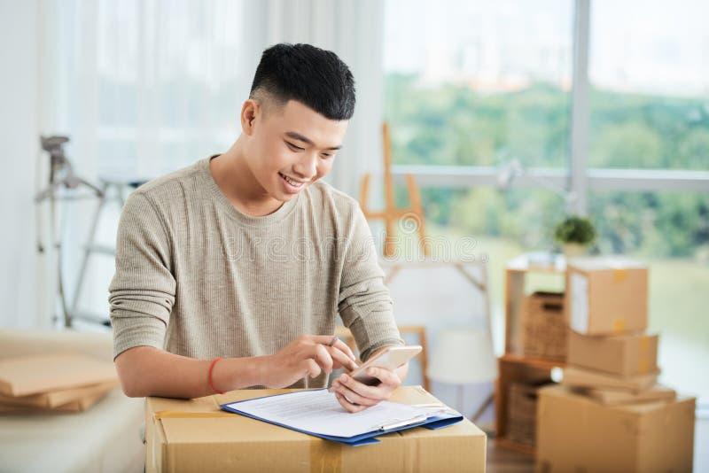 Maschio asiatico sorridente facendo uso dello smartphone al cartone fotografia stock