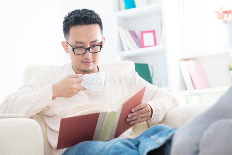 Maschio asiatico sudorientale che legge un libro immagine stock