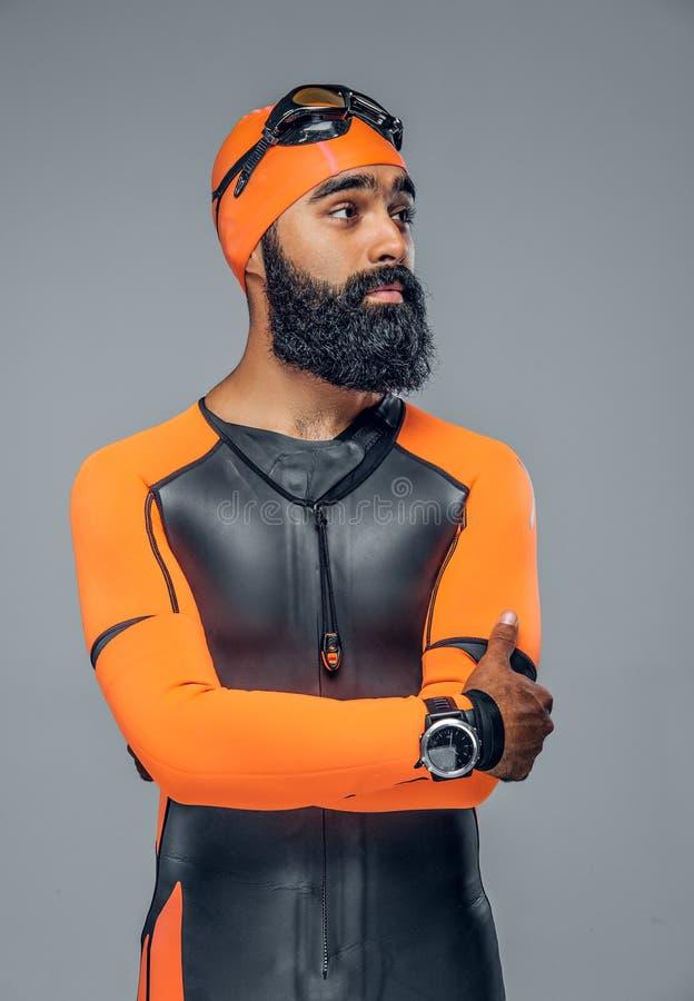 Maschio barbuto del subaqueo nel vestito arancio del neoprene isolato su gre immagini stock