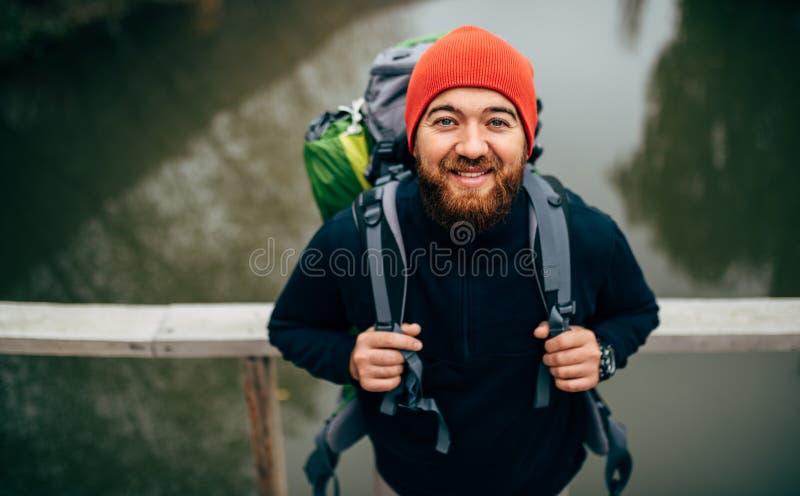 Maschio barbuto del viaggiatore che sorride e ritenere felice durante il trekking nel suo viaggio, posante contro il fiume immagine stock libera da diritti