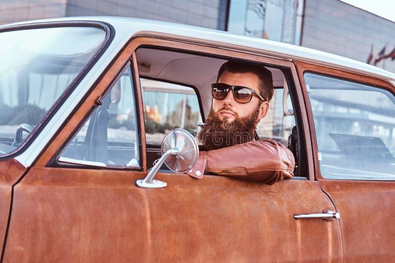 Maschio barbuto in occhiali da sole vestiti in bomber marrone che conduce una retro automobile immagini stock