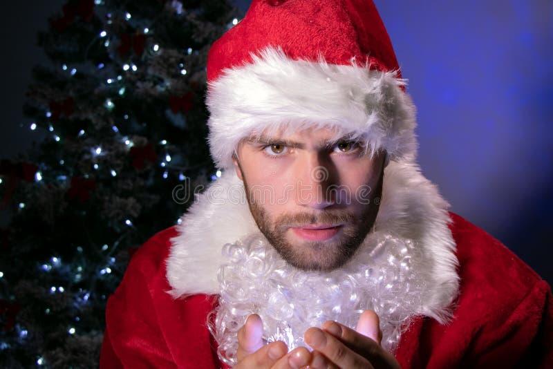Maschio bello Santa che tiene le luci in sua mano mentre esaminando macchina fotografica con l'albero di Natale nel fondo immagini stock libere da diritti