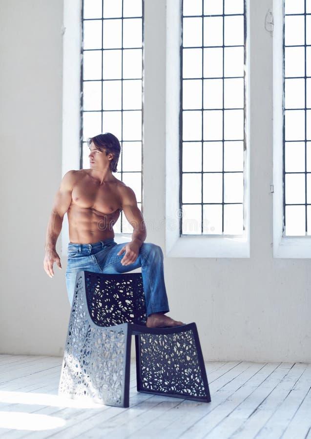 Maschio bello senza camicia con un corpo muscolare perfetto che posa mentre appoggiandosi una sedia nello studio immagini stock libere da diritti