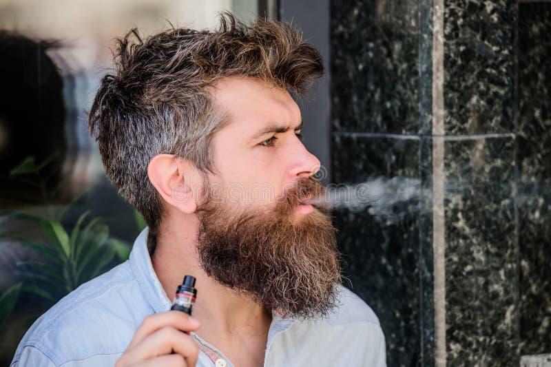 Maschio brutale barbuto che fuma sigaretta elettronica Pantaloni a vita bassa maturi con la barba dispositivo vaping della tenuta immagine stock