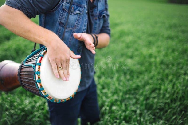 Maschio che gioca tamburo etnico all'aperto immagine stock