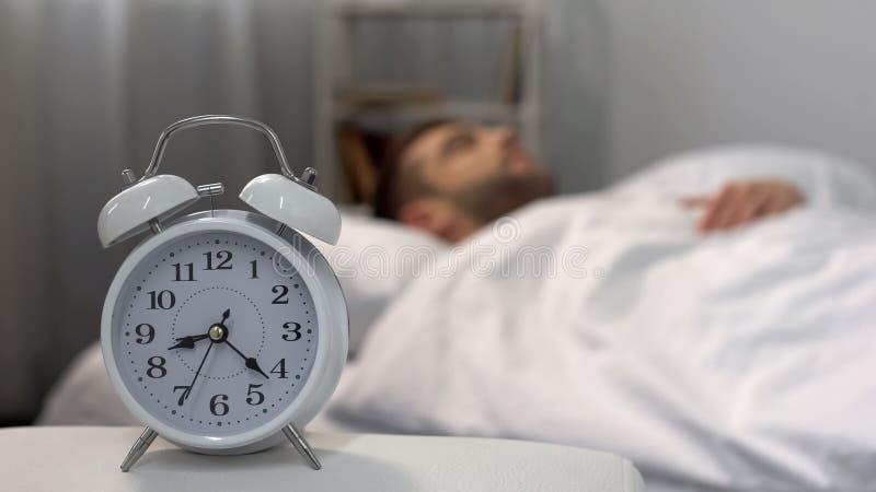 Maschio che si sveglia tardi nella mattina, allarme che suona al comodino, gestione di tempo immagini stock libere da diritti