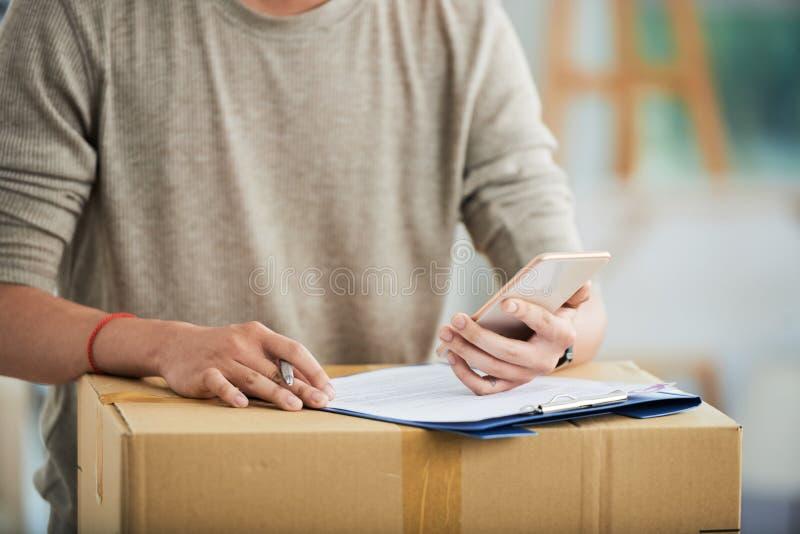 Maschio con la lavagna per appunti ed il cartone facendo uso dello smartphone fotografia stock libera da diritti