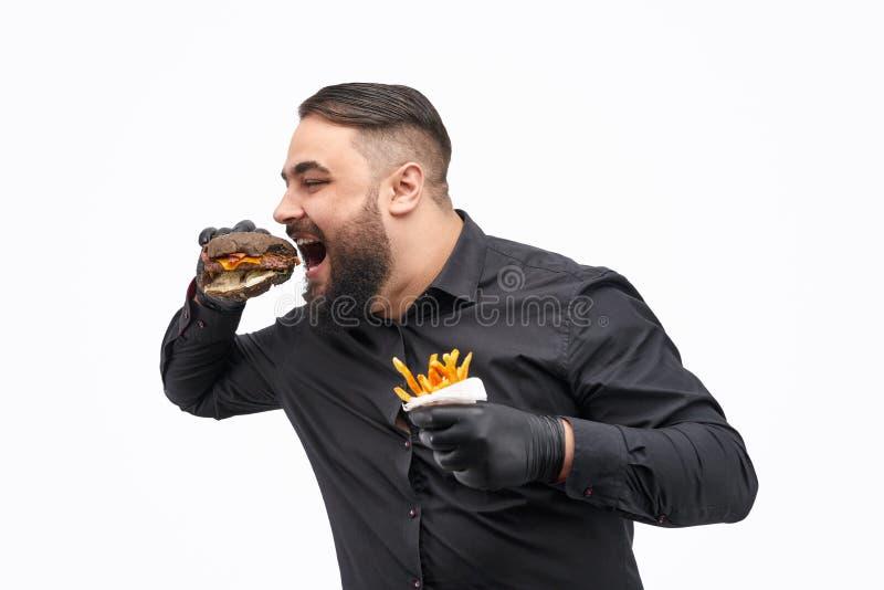 Maschio con le patate fritte che morde hamburger fotografie stock libere da diritti