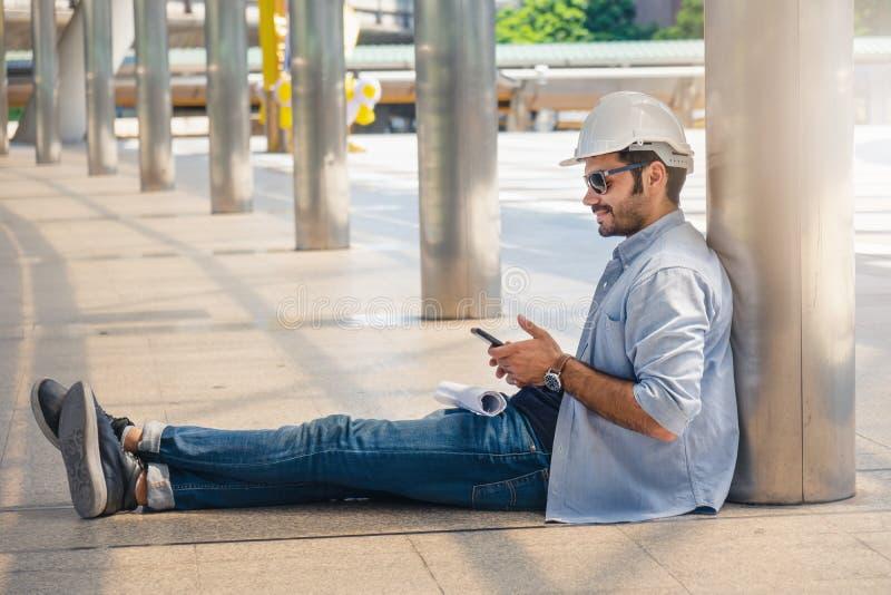 Maschio dell'ingegnere con il cappuccio dell'ingegnere capo che si siede sulla via al coridor esterno facendo uso dello smartphon fotografie stock