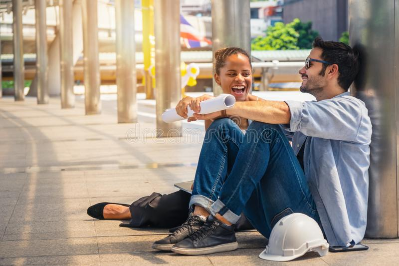 Maschio dell'ingegnere con il cappuccio dell'ingegnere capo e la carta di modello accanto alla conversazione con il partner femmi fotografie stock