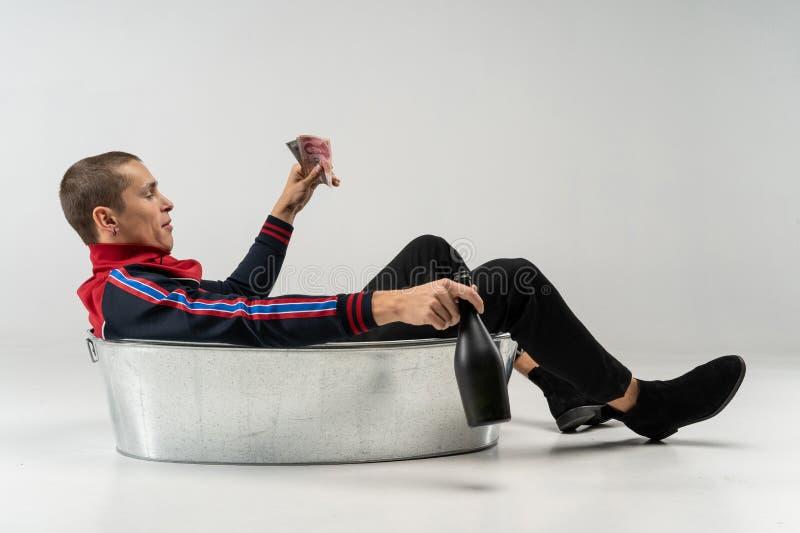 Maschio di modello bello con breve taglio di capelli nell'abbigliamento casual che si siede nel bagno del metallo in studio fotografia stock libera da diritti
