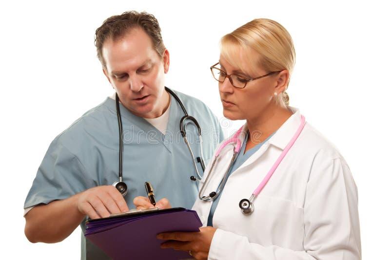 Maschio e femmina dottore Looking Over Files fotografia stock