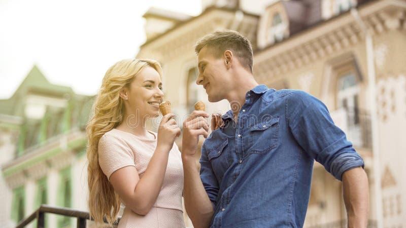 Maschio e femmina nell'amore che mangiano il gelato e che se esaminano, allegro fotografie stock libere da diritti