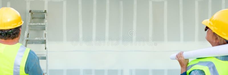 Maschio ed appaltatori femminili che trascurano l'insegna in bianco del muro a secco fotografia stock