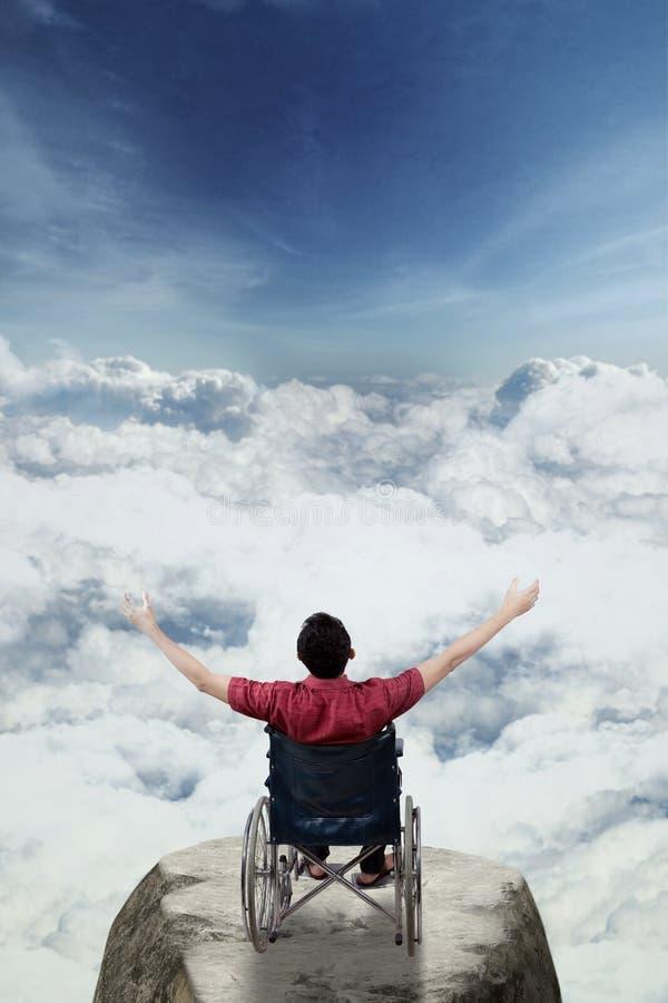 Maschio handicappato che solleva le mani nella montagna immagini stock libere da diritti