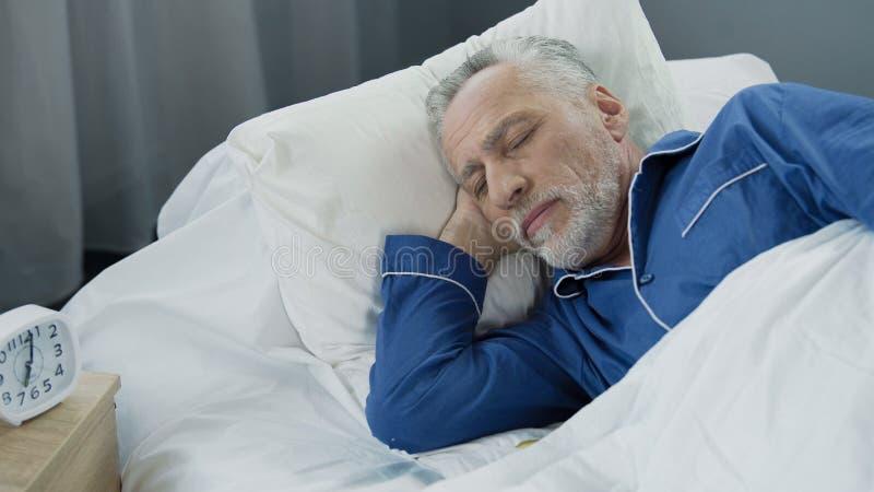 Maschio invecchiato che dorme a letto di mattina, sonno sano, tempo di recupero, primo piano fotografia stock
