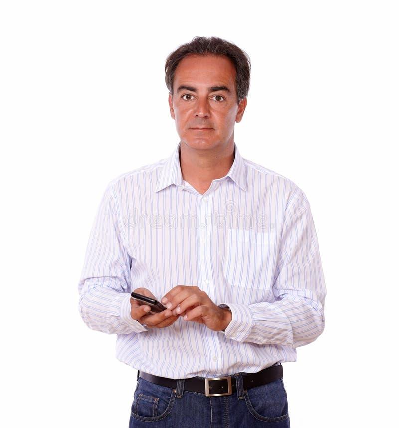 Maschio latino carismatico che manda un sms ad un messaggio fotografia stock libera da diritti