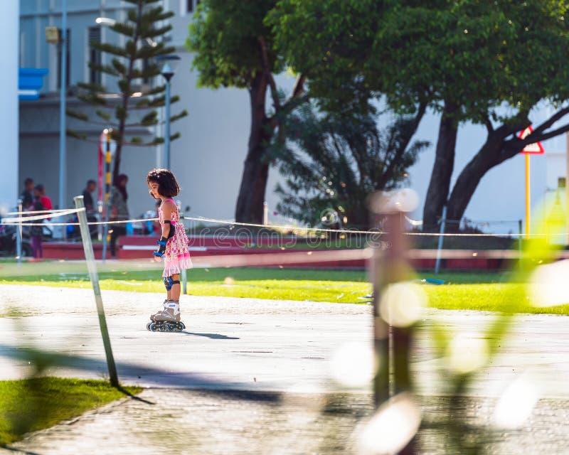 MASCHIO, MALDIVE - 27 NOVEMBRE, 2016: Bambina in un vestito rosa sui pattini di rullo Copi lo spazio per testo fotografia stock