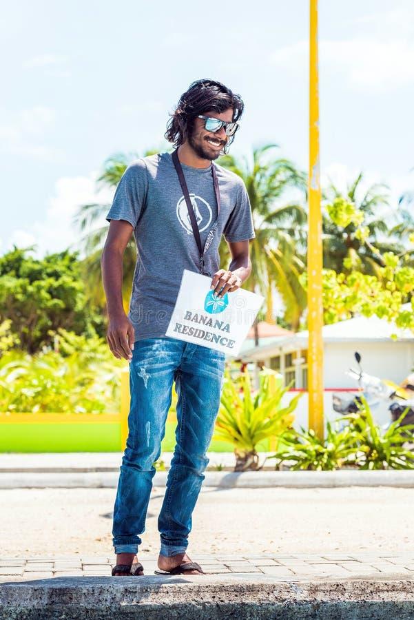 MASCHIO, MALDIVE - 27 NOVEMBRE, 2016: Uomo sorridente con un segno Copi lo spazio per testo verticale immagine stock