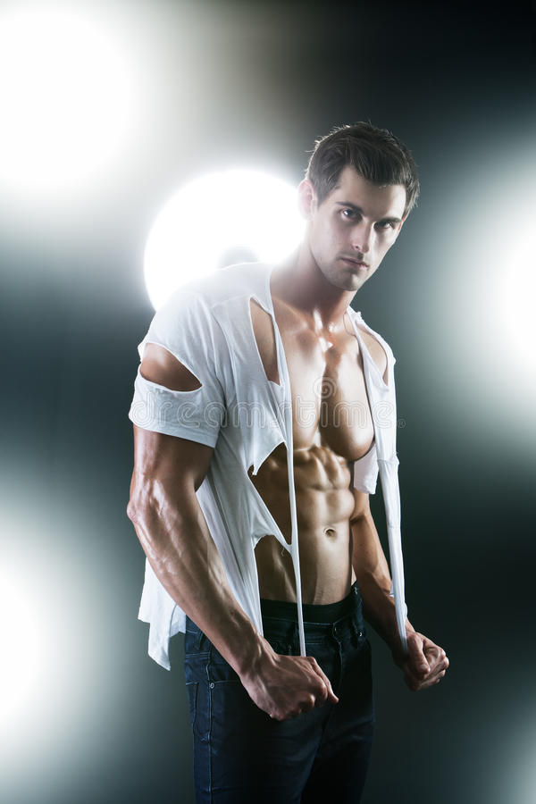 Maschio muscolare sexy in camicia strappata bianca fotografia stock libera da diritti