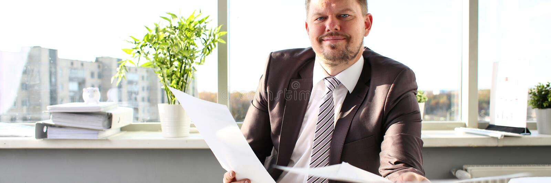 Maschio nella tenuta del legame e del vestito in carte del braccio all'ufficio fotografia stock