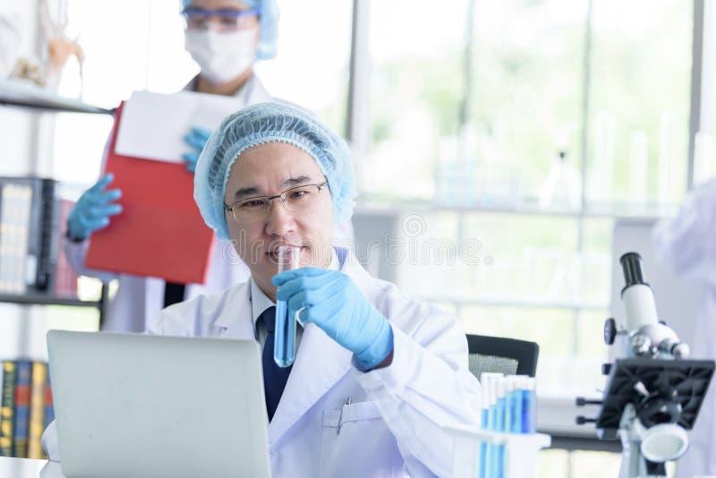 Maschio senior asiatico dello scienziato che ricerca e che impara in un laboratorio fotografia stock libera da diritti
