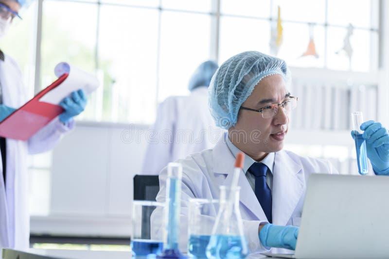 Maschio senior asiatico dello scienziato che ricerca e che impara in un laboratorio fotografia stock