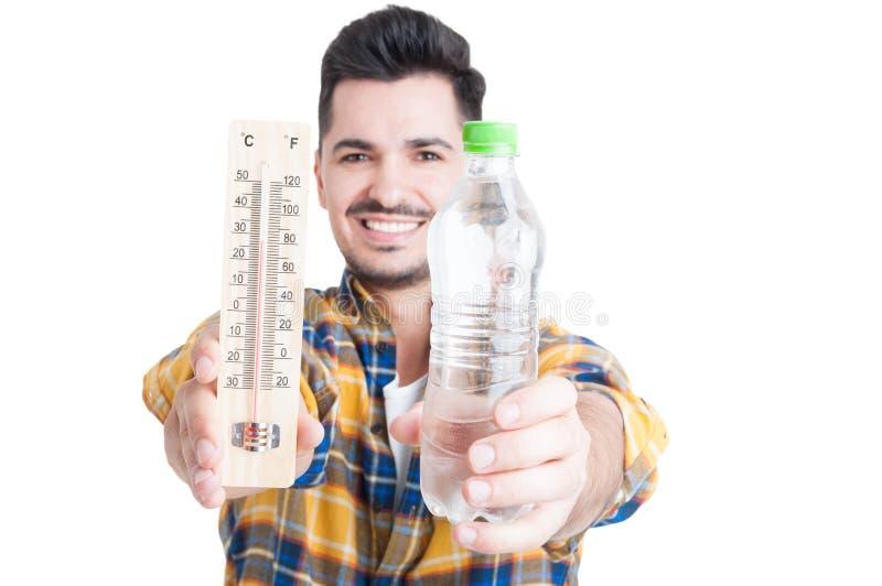 Maschio sorridente che tiene una bottiglia di acqua e di un termometro immagini stock