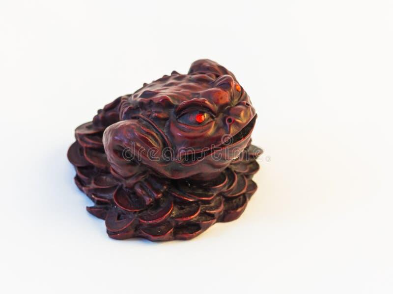 Mascotte d'argent liquide - Chan Chu - une figurine brune de grenouille se reposant sur des pi?ces de monnaie images stock