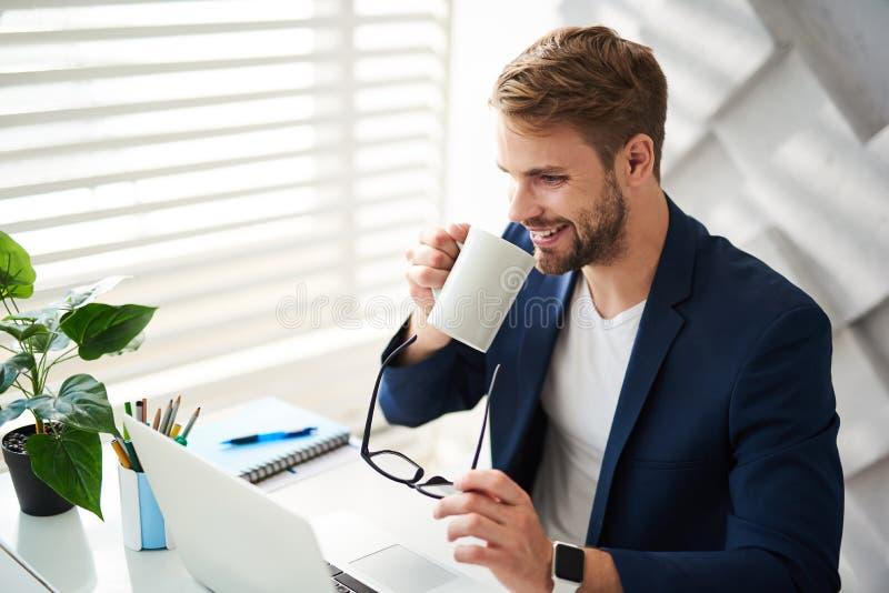 Masculin satisfait ayant la pause-café au travail image libre de droits