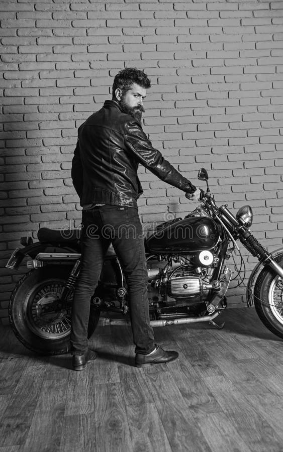 Masculine hobby concept. Hipster, brutal biker on serious face in leather jacket sits down on motorcycle. Man with beard. Biker in leather jacket near motor stock images