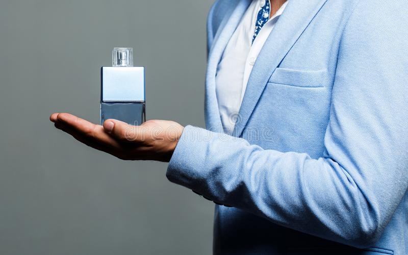 Masculine perfume, bearded man in a suit. Man perfume, fragrance. Male holding up bottle of perfume. Perfume or cologne stock image