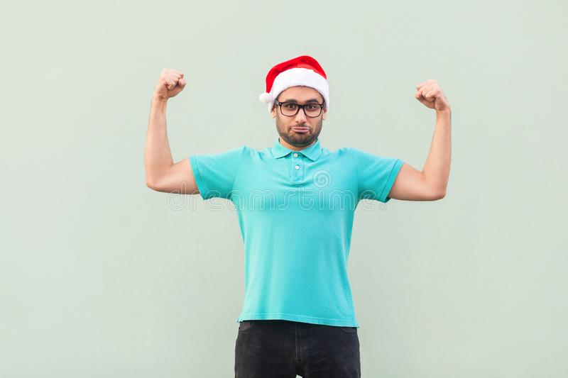 Masculinity bearded man posin looks like bodybuilder, showing bi. Ceps, looking at camera and smiling. Studio shot stock photo