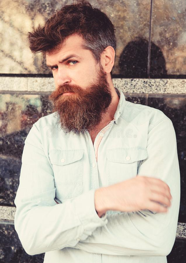 Masculinity concept. Guy looks suspicious. Hipster with tousled hair hold arms crossed on chest. Man with beard and. Mustache on thoughtful, pensive face, black stock photo