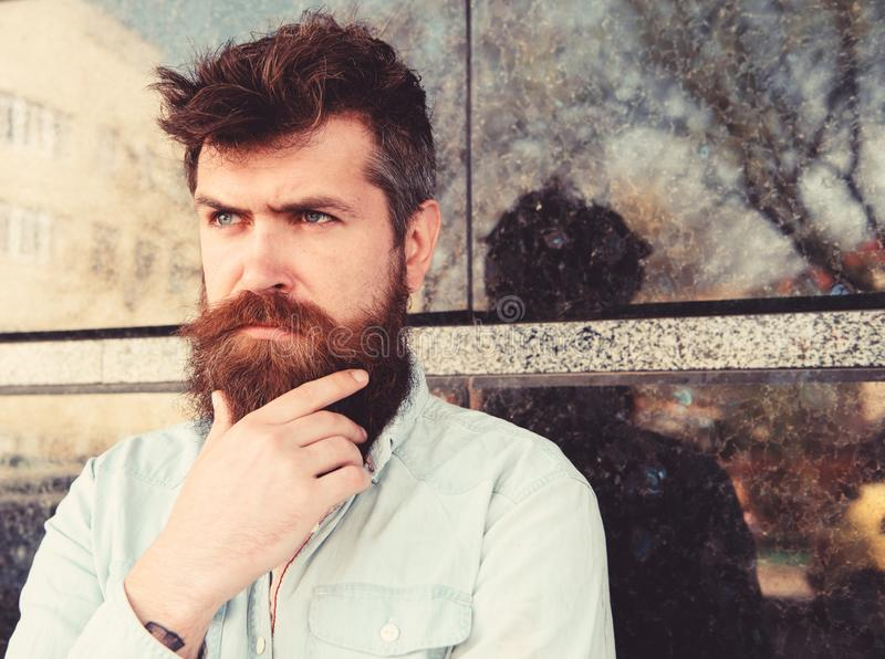 Masculinity concept. Hipster with tousled hair touches beard while looking into distance. Guy looks suspicious. Man with. Beard and mustache on thoughtful royalty free stock image