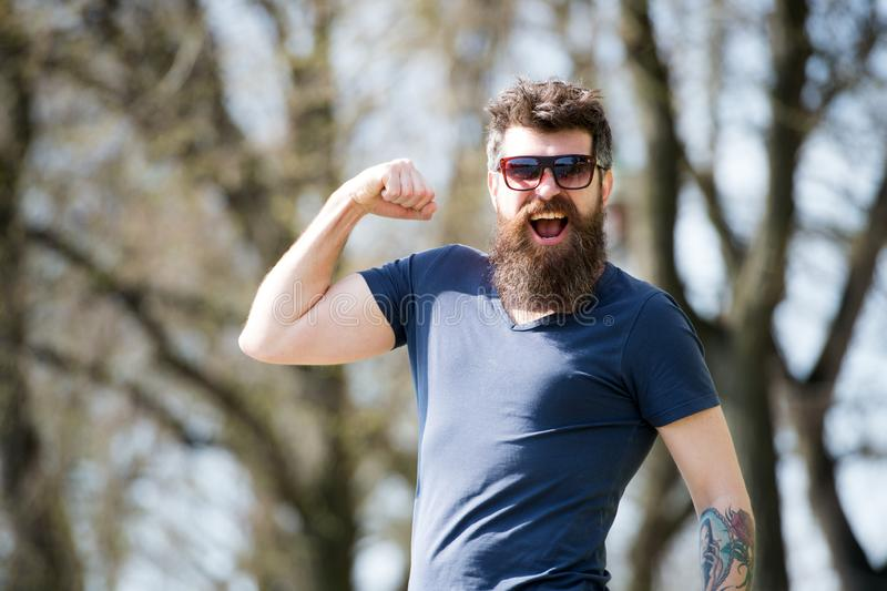 Masculinity concept. Macho with beard look confident brutal in sunglasses. Bearded guy muscular arm power gesture. Man royalty free stock photo