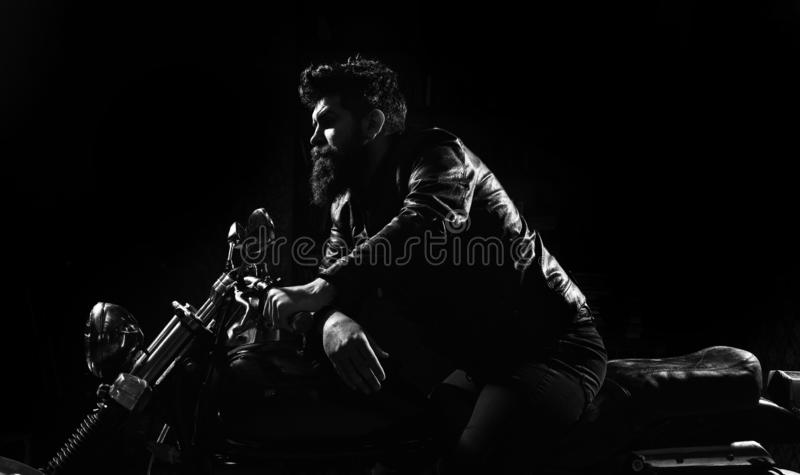 Masculinity concept. Macho, brutal biker in leather jacket riding motorcycle at night time, copy space. Man with beard. Biker in leather jacket sitting on royalty free stock photo