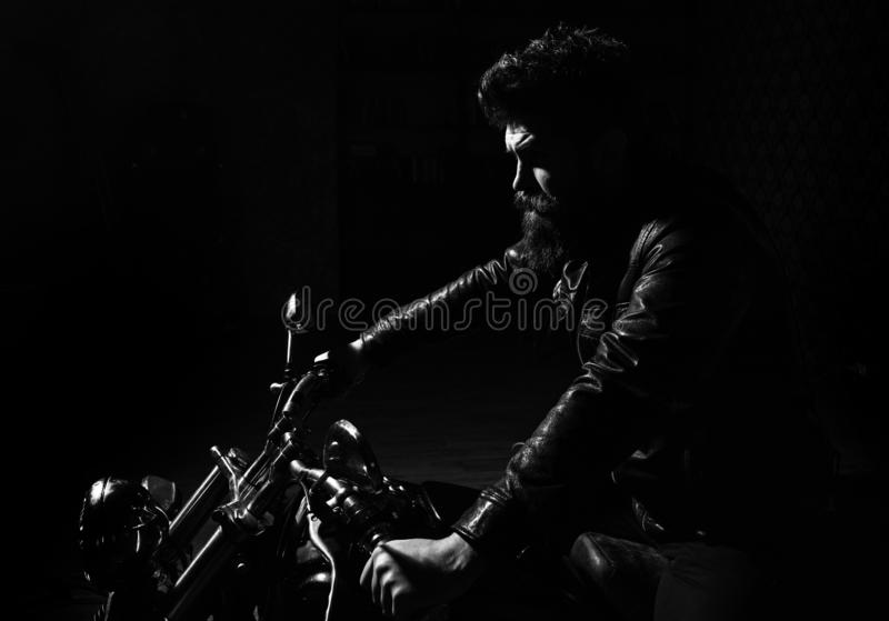 Masculinity concept. Man with beard, biker in leather jacket sitting on motor bike in darkness, black background. Macho. Brutal biker in leather jacket riding stock images
