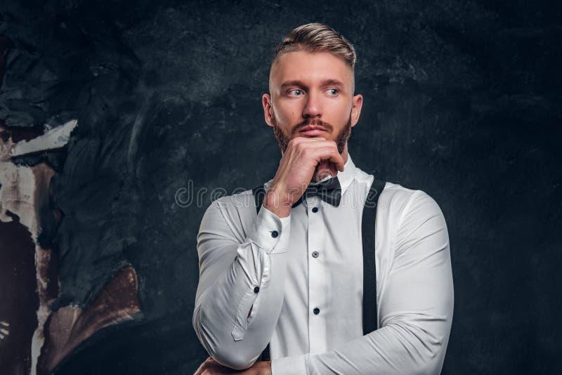 Masculino pensativo pensando alrededor de algo importante Hombre joven elegante vestido en camisa con la presentación de la corba foto de archivo libre de regalías