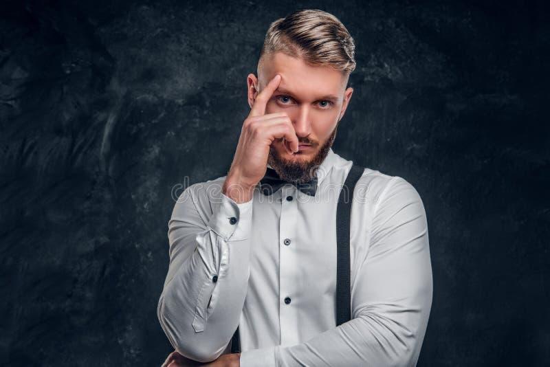Masculino pensativo pensando alrededor de algo importante Hombre joven elegante vestido en camisa con la presentación de la corba foto de archivo