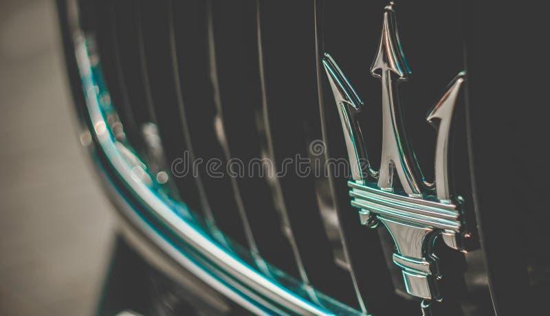 Maserati标志,前保险杆视图,照片被拍在汽车商展 图库摄影