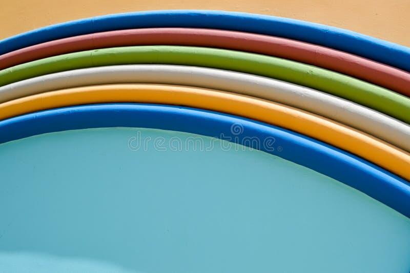 Masern Sie abstrakten bunten hellen bunten festlichen Regenbogenbogen des dekorativen Stucksteins auf einem blauen und gelben Hin lizenzfreie stockfotografie