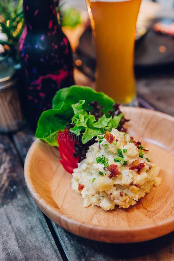 Mashed potato with bacon served with salad in wooden plate with a glass of beer in the background royalty free stock photography