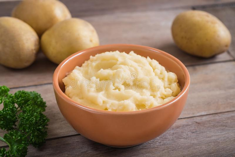 Mashed potato in bowl and fresh potatoes on wooden table royalty free stock photography