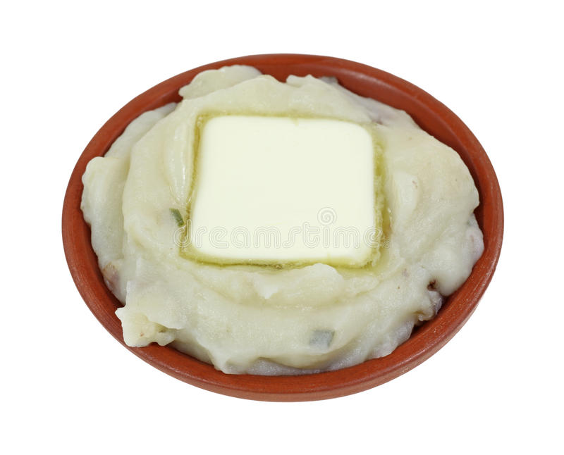 Mashed Potato With A Pat Of Butter. A serving of red skinned mashed potatoes with a pat of butter in a serving dish on a white background stock photo