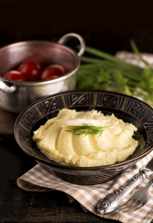Mashed potatoes in bowl on wooden table stock photo