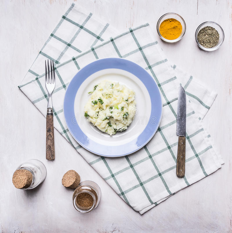 Mashed potatoes with onions on a blue plate with a knife and fork spices on a checkered napkin on rustic wooden background top vie stock image