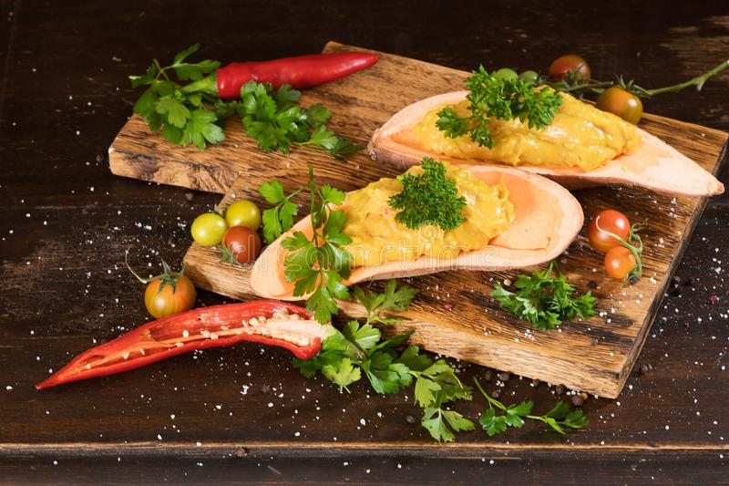 Mashed sweet potato with pepers chilli, tomatoes and greenery on a dark wooden board background. stock photo